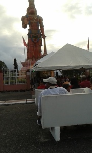 A view of devotees listening to chanting at the 85 ft Karya Siddhi Hanuman Murti at DYC Carapichaima